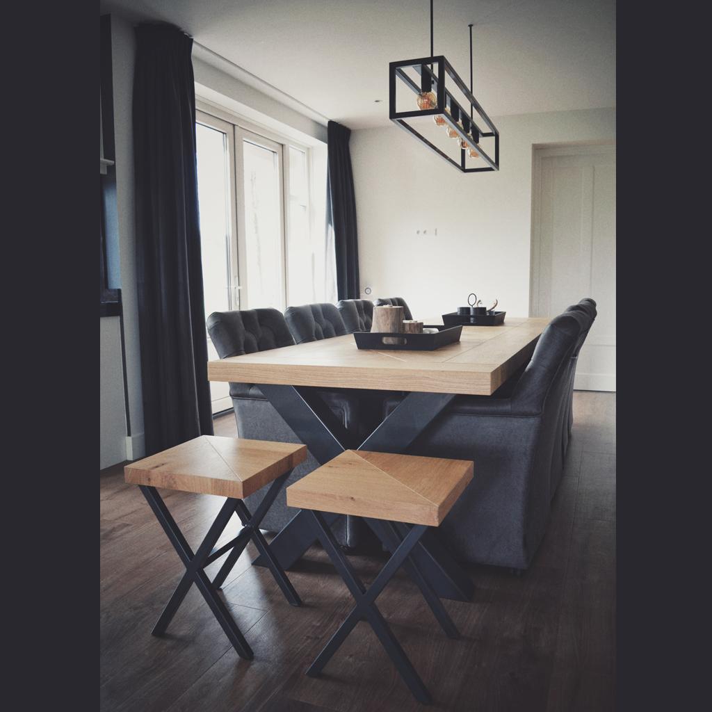 Het staal van de lamp vormt een eenheid met de kruispoot van de tafel. De bedrading van de lamp is wegwerkt in de ophanging aan het plafond door een strak stalen buisje waardoor het snoer nauwelijks zichtbaar is.