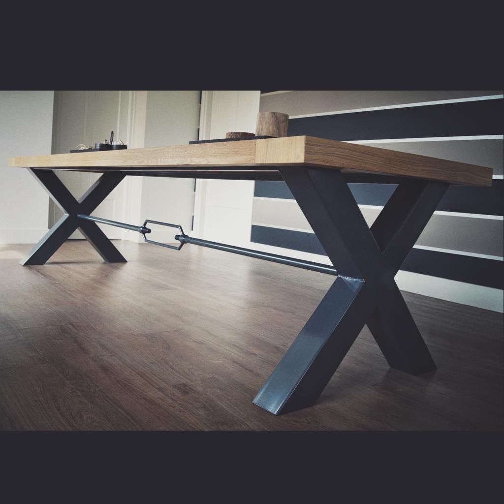 Een handgemaakte spanwartel tussen de kruispoten geeft de tafel extra karakter.